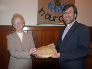 Trevor Jamison hands over the award plaque to Magaret Steele, in front of the new eco-banner